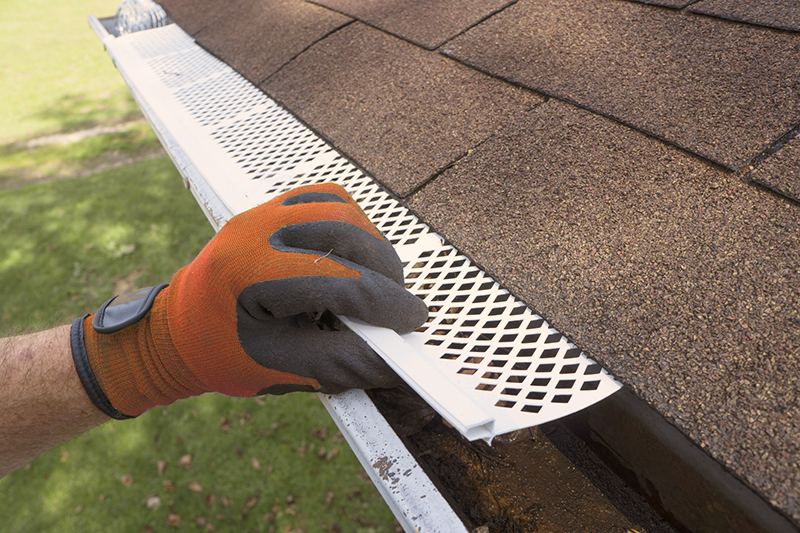 Person wearing gloves installing gutter guards
